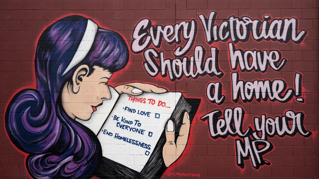 "A mural of a girl reading and a sign that reads ""Every Victorian should have a home!"""